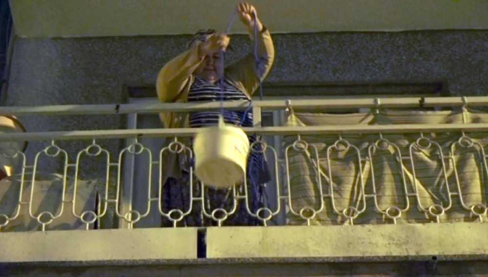 Her gün evinin balkonundan aşağı sarkıttığı kova ile sokak hayvanlarını besliyor