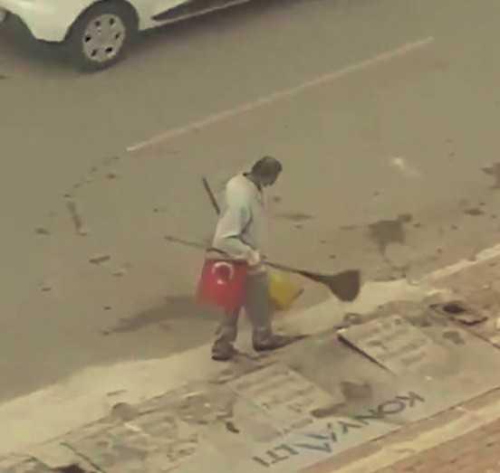 Yerde bulduğu Türk bayrağını süpürgesine takarak işine devam etti